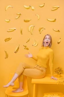 Frau und sich hin- und herbewegende bananen in einer gelben szene