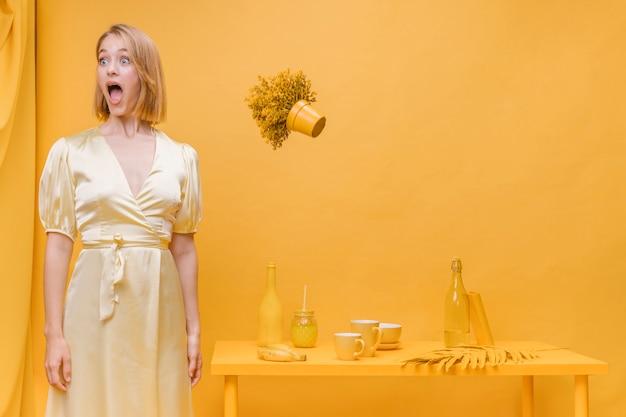 Frau und sich hin- und herbewegender blumentopf in einer gelben szene