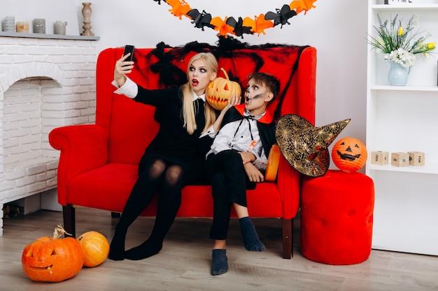 Frau und sohn haben eine lustige zeit auf dem roten sofa und machen ein selfie. emotion und halloween