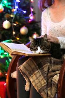 Frau und süße katze sitzen auf schaukelstuhl und lesen das buch vor dem weihnachtsbaum