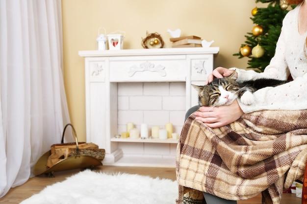 Frau und süße katze sitzen auf schaukelstuhl vor dem kamin