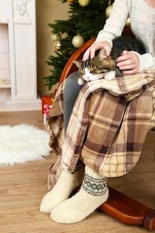Frau und süße katze sitzen auf schaukelstuhl vor dem weihnachtsbaum