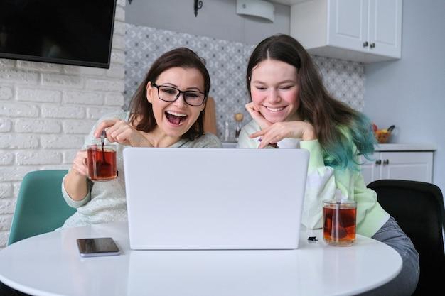 Frau und teenager sitzen zu hause in der küche, trinken tee zusammen und betrachten laptop-monitor
