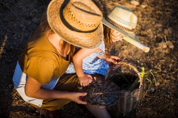 Frau und tochter, die geerntetes gemüse im korb betrachten