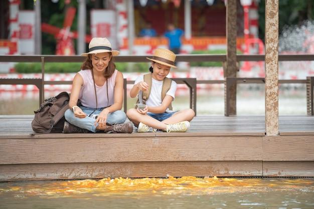 Frau und tochter füttern fische in einem teich