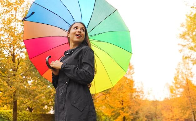 Frau unter regenbogenregenregenschirm im park, der zur seite schaut