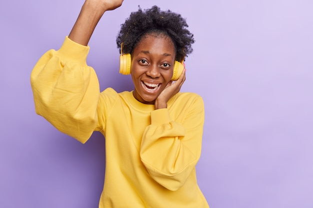 Frau unterhält zu hause während der quarantäne von covid 19 hört musik in kopfhörern genießt lieblingslied isoliert auf lila