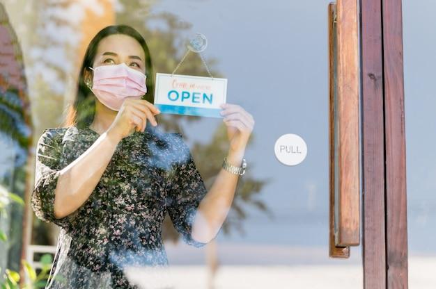 Frau unternehmerin frau eröffnet café und essen, nachdem die regierung quarantänemaßnahmen zur verhinderung von epidemien lockern.