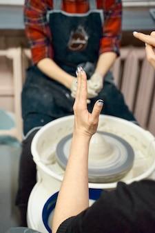 Frau unterrichtet die töpferei auf töpferscheibe, meisterklasse, werkstatt. kreatives hobbykonzept
