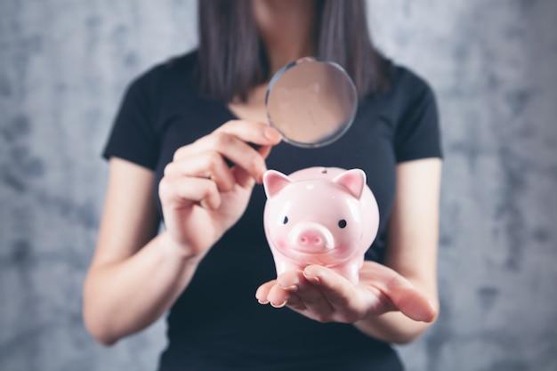 Frau untersucht ein sparschwein mit einer lupe