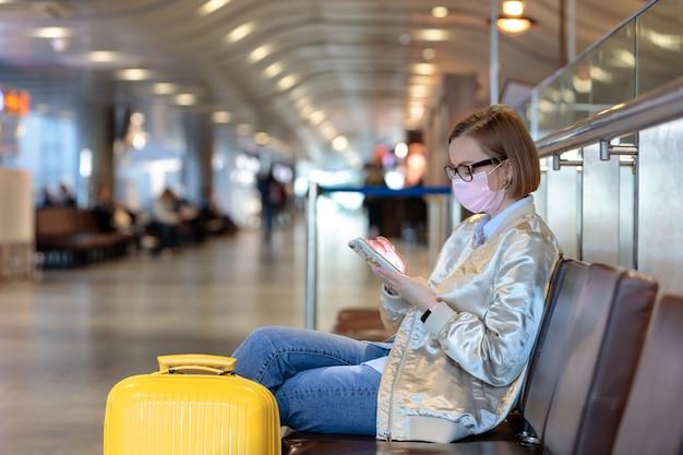 Frau verärgert über flugstornierung, schreibt nachricht, sitzt in fast leerem flughafenterminal