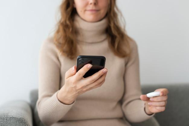 Frau verbindet intelligenten lautsprecher mit telefon