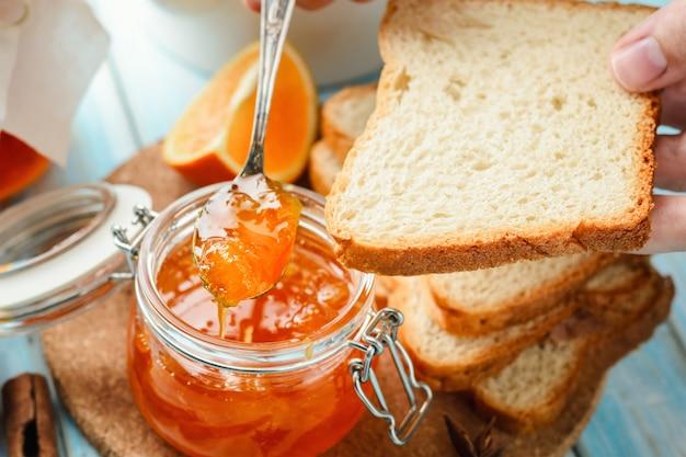 Frau verbreitet scheiben brot mit orangenmarmelade