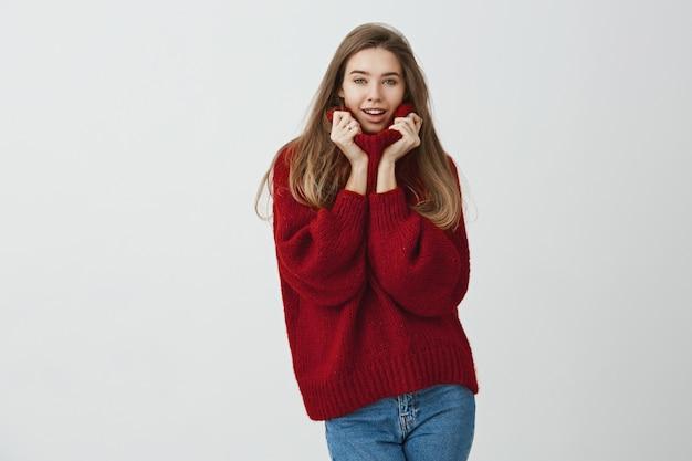 Frau verführt ihren kollegen. porträt der schönen modernen frau im losen pullover, der kragen mit beiden händen hält, während mit wunsch starrt, sinnlich lächelt und steht.