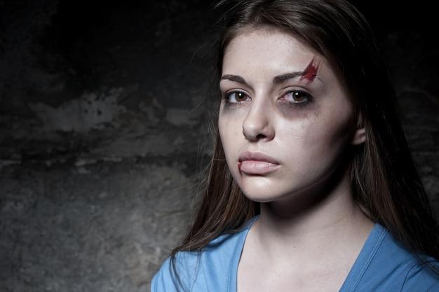 Frau verprügelt. junge verprügelte frau, die kamera anschaut, während sie gegen dunkle wand steht