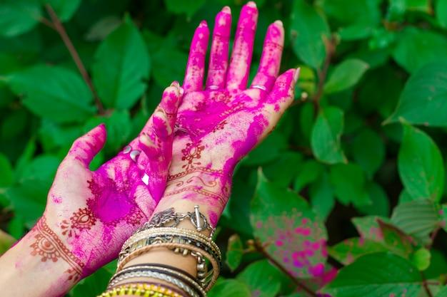 Frau verschmierte hände mit henna-tätowierung und armbänderschmuck bunte rosa violette holi-staubpulverfarbe glückliches traditionelles indisches hochzeitsferien-sommerkulturfestival-konzept grüner blätterhintergrund