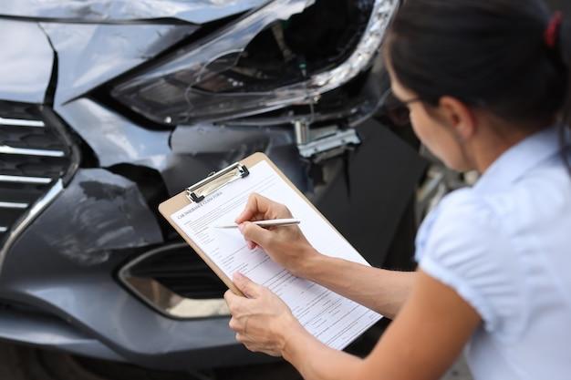 Frau versicherungsagent ausfüllen von papierkram in der nähe von autowrack nahaufnahme schätzung der kosten von