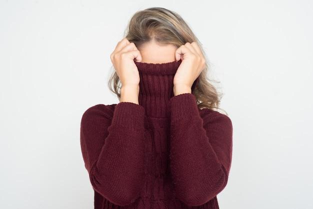 Frau versteckt gesicht im rollkragenpullover