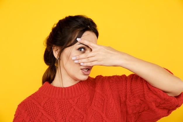 Frau versteckt ihr gesicht und schaut durch ihre finger.