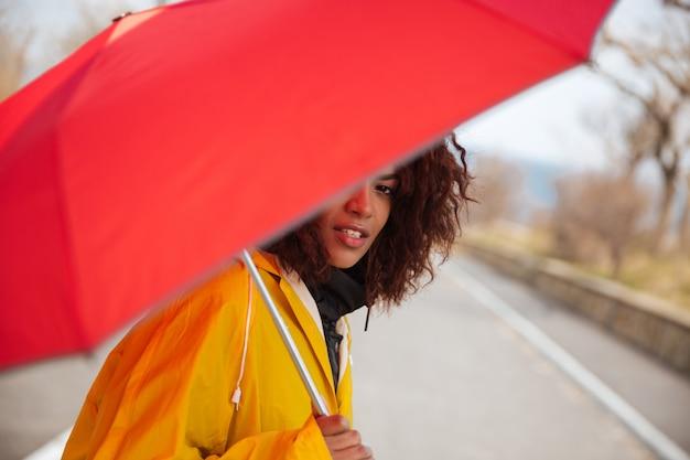 Frau versteckt sich hinter regenschirm