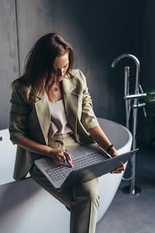 Frau versteckt sich zu hause im badezimmer mit ihrem laptop, um zu arbeiten.