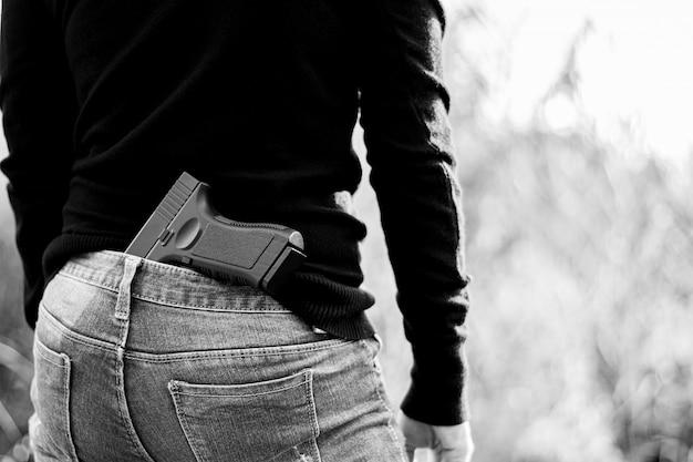 Frau versteckte ein gewehr das rückseitige - gewalttätigkeits- und verbrechenkonzept.