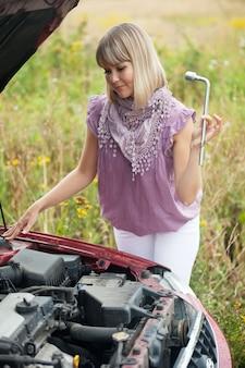 Frau versucht, das auto zu reparieren