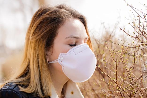 Frau versucht, den geruch des frühlings in einer schutzmaske zu riechen