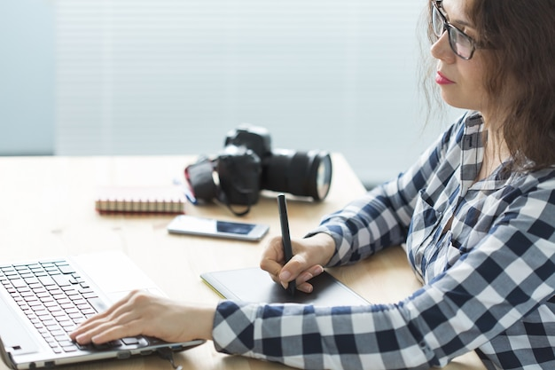 Frau verwenden designer-tablette bei der arbeit am laptop.