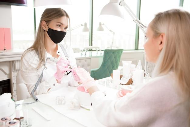 Frau verwenden elektrische nagelfeilenbohrmaschine im schönheitssalon. perfekter nagel-maniküre-prozess in nahaufnahme.