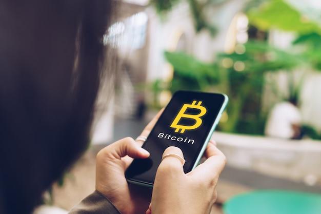 Frau verwenden gadget mobile smartphone geld verdienen online kaufen bitcoin mit zeichen symbol pop-up.