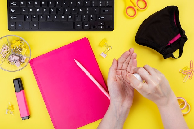 Frau verwendet ein antiseptisches gel während der arbeit am computer, gelber hintergrund.