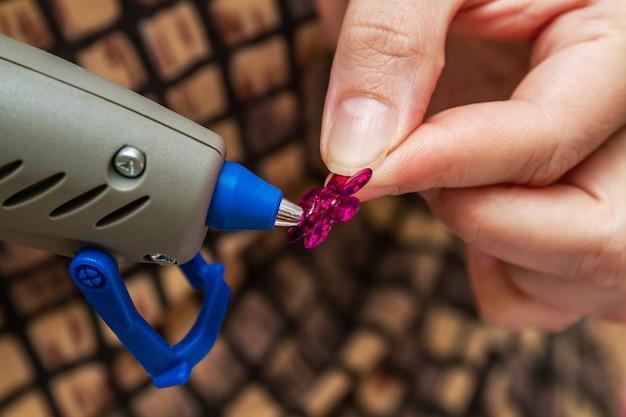 Frau verwendet heißklebepistole in handgefertigten anwendungen. needlewoman klebt pailletten.