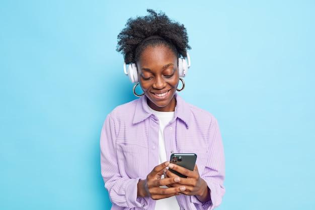 Frau verwendet moderne technologien hält smartphone wählt lied aus playlist zum anhören trägt drahtlose kopfhörer auf den ohren, gekleidet in stylische kleidung