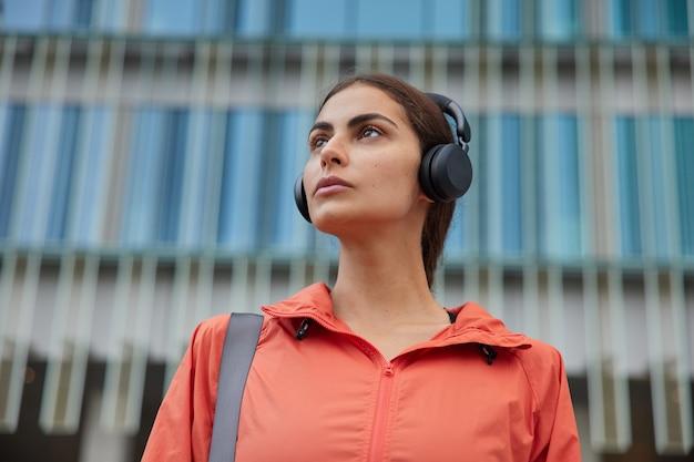 Frau verwendet moderne technologien während des sporttrainings, das sich irgendwo konzentriert, hört musik mit kopfhörern, posiert gegen modernes gebäude