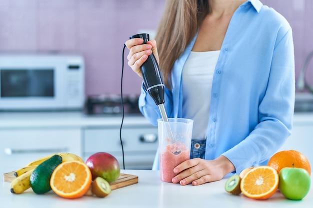 Frau verwendet stabmixer, um frische früchte zu mischen, um diät-smoothie in der küche zu hause zuzubereiten