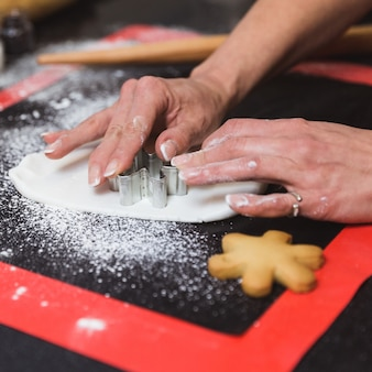 Frau verziert weihnachtslebkuchenplätzchen mit puderzucker-glasurschneeflocke. weihnachtsgeschenk, hausgemachter lebkuchen