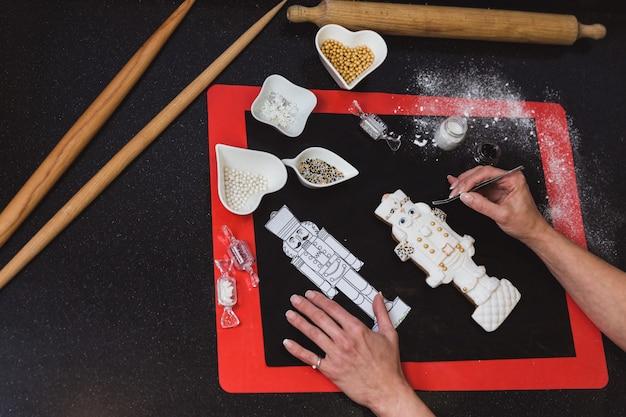 Frau verziert weihnachtslebkuchenplätzchen mit puderzuckerglasurnussknacker. weihnachtsgeschenk, hausgemachter lebkuchen