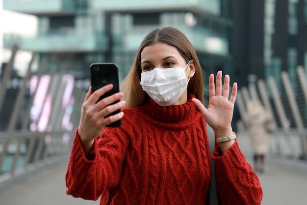 Frau videoanruf im freien. glückliche fröhliche frau mit chirurgischem maskenvideo, das in der modernen stadtstraße chattet.