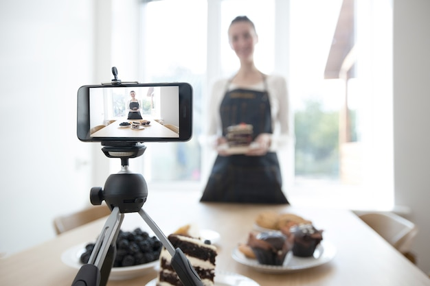 Frau vlogger, der video für nahrungsmittelkanal aufzeichnet. kocher shef, der ein video für vlog mit einem telefon aufzeichnet