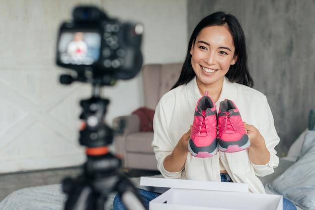 Frau vlogging mit ihren sportschuhen