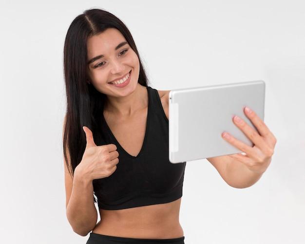 Frau vlogging zu hause mit tablette, während sie trainiert und daumen aufgibt