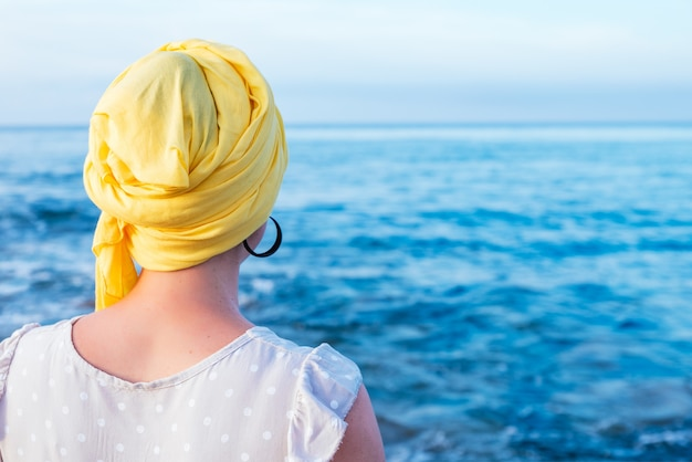 Frau von hinten mit gelbem schal, der ihren kopf bedeckt, ohne haare, die den seehorizont betrachten
