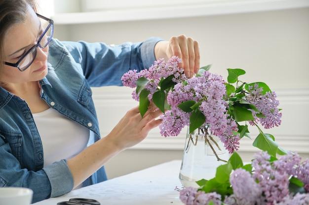 Frau von mittlerem alter, die blumenstrauß von den lila niederlassungen macht