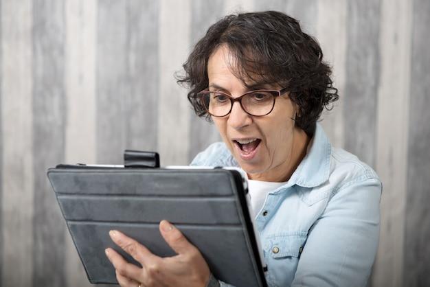 Frau von mittlerem alter, die einen entfernten anruf im internet macht