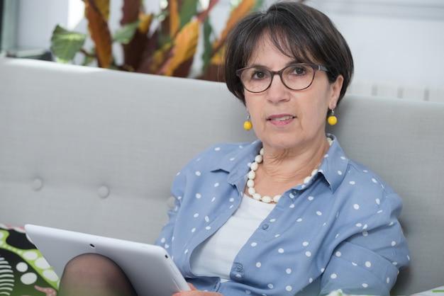 Frau von mittlerem alter, die zu hause digitale tablette verwendet