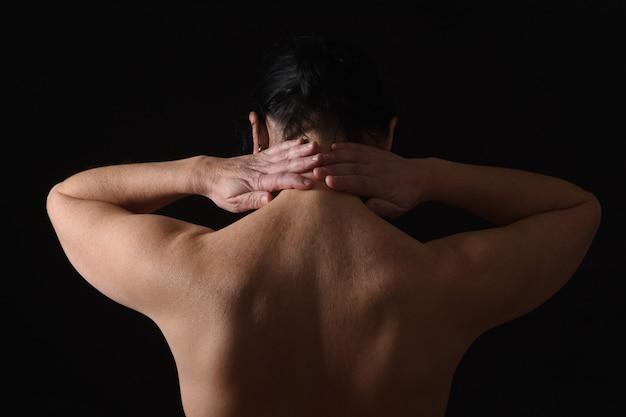 Frau von mittlerem alter mit den schmerz im stutzen auf schwarzem hintergrund