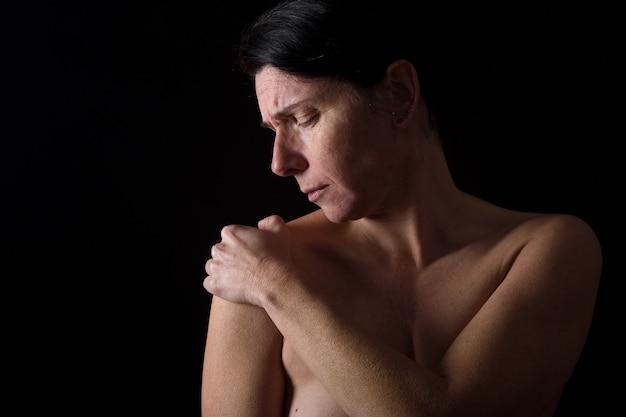 Frau von mittlerem alter mit schulterschmerzen