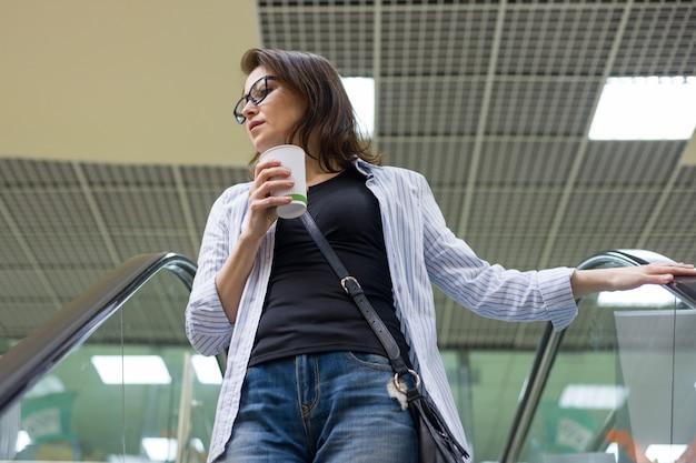 Frau von mittlerem alter mit tasse kaffee im einkaufszentrum