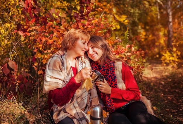 Frau von mittlerem alter und ihre tochter, die tee im wald trinkt